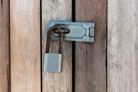 Close up of padlock and old metal hasp and staple on an old wooden door