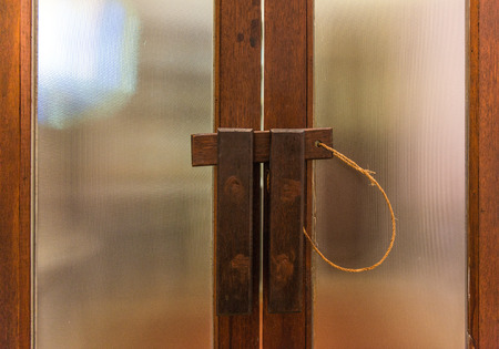 Closeup of a vintage wooden latch on a door glass photo