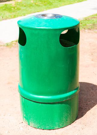 a green trashcan and Ashtray photo