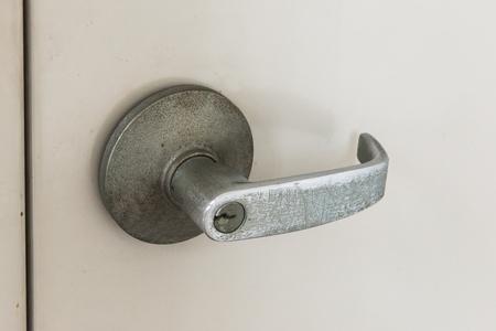 nickle: Detail of a metallic knob on gray door horizontal