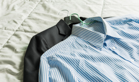 formal dressing: closeup Mens classic shirts and suit on the bed