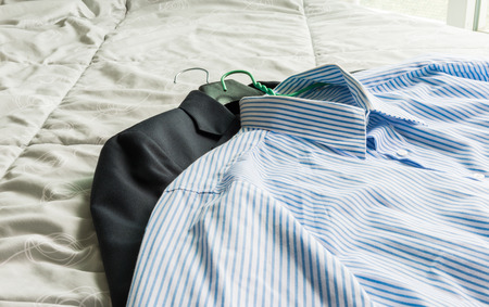 laundry hanger: closeup Mens classic shirts and suit on the bed