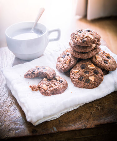 Chocolate chip cookies on napkin and hot tea on wooden table. Stacked chocolate chip cookies close up. split toning color image photo