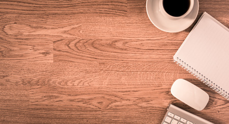 Office table with notepad, computer and coffee cup and computer mouse. View from above with copy space