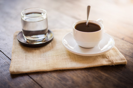 gunny: Cup of coffee on a wooden table with glass of water on the Sackcloth bags Stock Photo