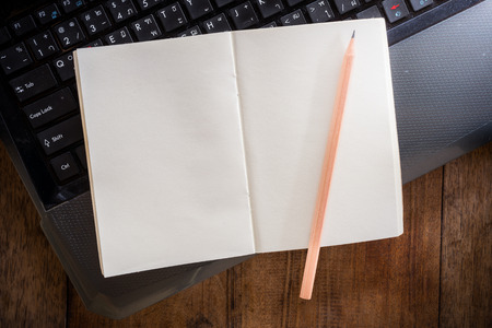 write background: Blank notebook with pencil on Laptop and wooden table. The view from the top