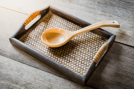 chinese bamboo: wooden spoon on Chinese bamboo woven tray on wooden background