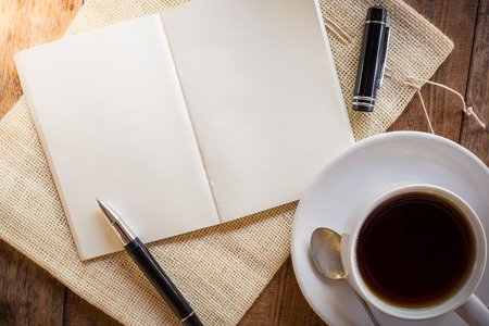 Blank notebook with pen and cup of coffee on wooden table. The view from the top photo