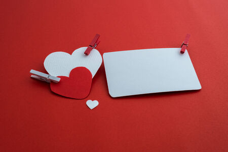 clothespin: valentines paper hearts with a blank business card and Clothespin on a red background