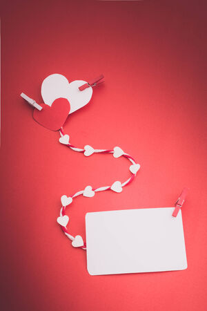 clothespin: valentines paper hearts with a blank business card and Clothespin on a red background , valentines day , day valentine , postcard