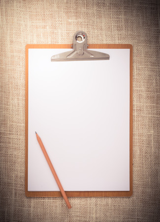 wooden clipboard on a old sackcloth background, with regular white blank paper. photo