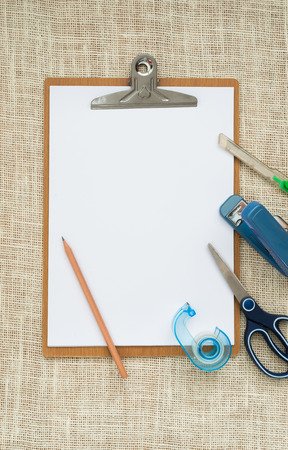 wooden clipboard on  sackcloth background, with regular white blank paper and office stationery. photo