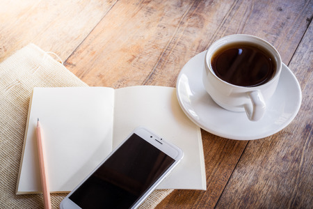 web surfing: Cup of coffee on a wooden table with glass of water on the Sackcloth bags and smartphone and notebook and pencil. Simple workspace or coffee break with web surfing