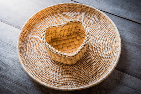 Empty a heart-shaped rattan basket and tray isolated on wooden table background photo
