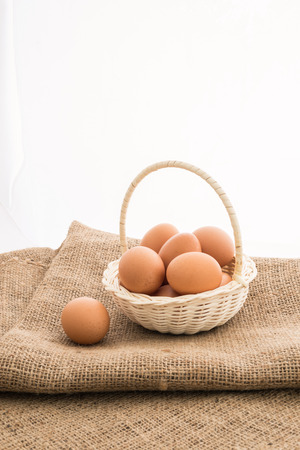gunny: Closeup of Chicken eggs in the bamboo basket over sackcloth Stock Photo