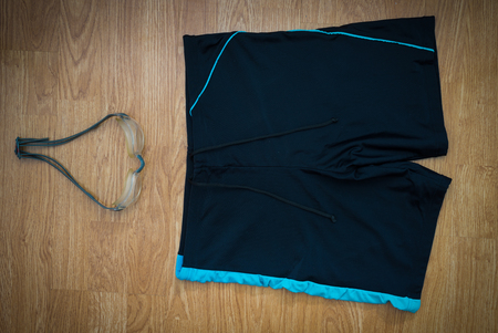 swimming trunks: glasses and Swimming trunks on wooden background