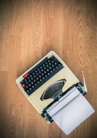 Vintage typewriter and a blank sheet of paper, retro style photo