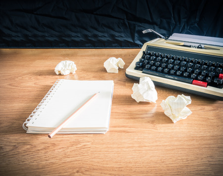 Vintage typewriter and a blank notebook of paper, retro style photo