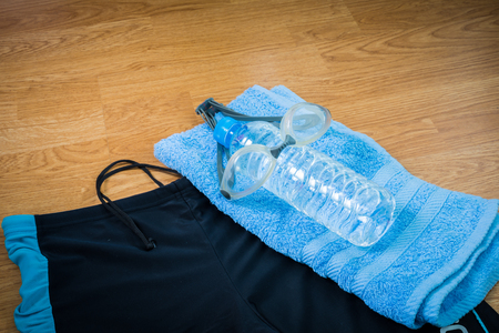 swimming trunks: glasses, Swimming trunks, water Bottle and towel on wooden background Stock Photo