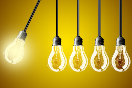 economic activity: Idea concept on yellow background. Perpetual motion with light bulbs