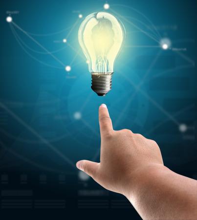Bulb light on man finger on blue background photo