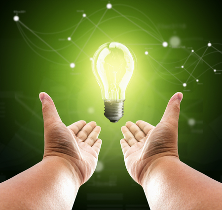 Bulb light on two hand of man on green background photo