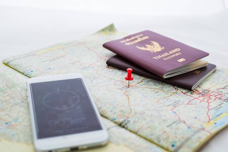 destinations: Passport on map and compasses in smartphones. red pin is mark destinations. Focus at red pin