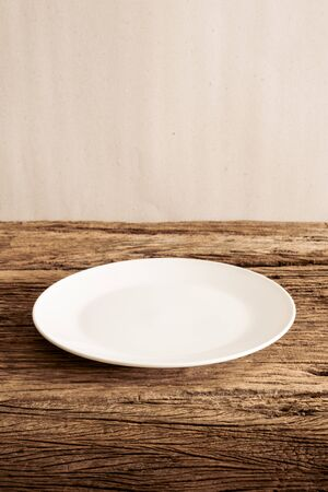 tabletop: Empty Plate on wooden tabletop against grunge wall. vintage tone
