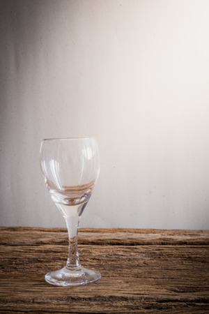 tabletop: wine glass on wooden tabletop against grunge wall. vintage tone Stock Photo