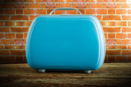 tabletop: modern tourist luggage on wooden tabletop against grunge wall. vintage tone