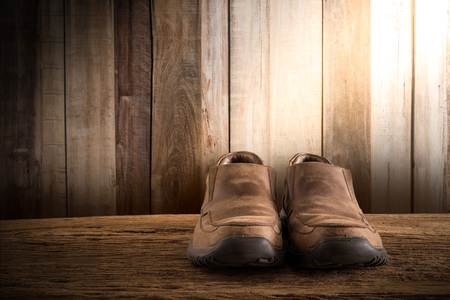 Still life with Men's Shoes on wooden tabletop against grunge wall. vintage tone