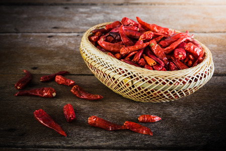 chili peppers: Dried Chili Peppers Bamboo Basket on wooden table. vintage tone Stock Photo