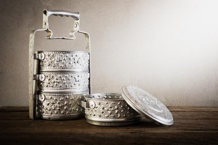 tiffin: metal Tiffin carrier, thai food carrier on wooden table background.vintage color toned image