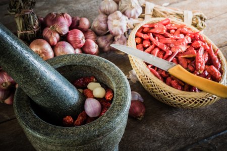 dry chili pepper and red onion and garlic and stone mortar on an old wooden background. vintage tone photo