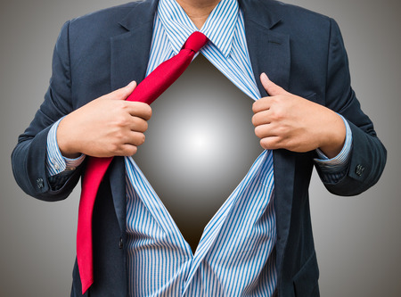 Businessman showing a superhero suit underneath his suit, isolated on white background.  Foto de archivo