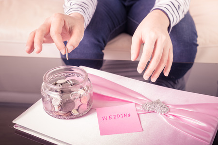 Hand putting a coin into glass jars with 'wedding' text. wedding concept , saving concept. focus at hand hold coin