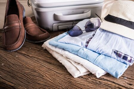 folded clothes: travel, summer vacation, tourism and objects concept, close up of folded clothes, smartphone and sunglasses, leather shoes on wooden table