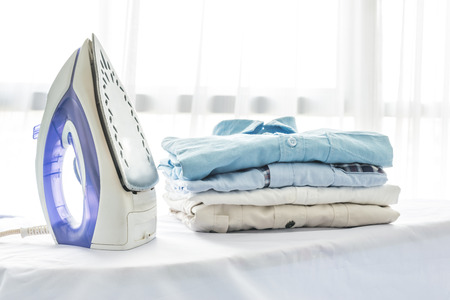 orden y limpieza: plancha, ropa, tareas domésticas y objetos concepto, de cerca de hierro y ropa en la mesa en casa Foto de archivo