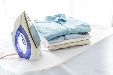 ironing, clothes, housework and objects concept, close up of iron and clothes on table at home