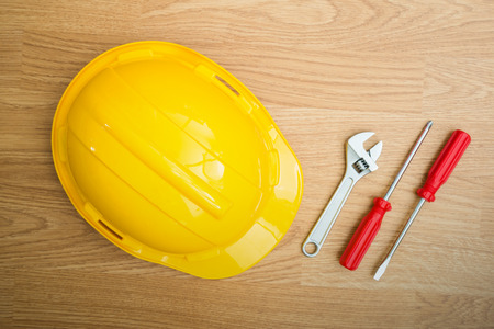 Yellow Safety Helmet Hat and screwdriver,wrench on Wood background