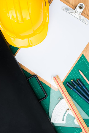 paper board: Yellow Safety Helmet Hat and clipboard and Drawing Tools, Cutting pads, Drawing Paper Bags  on Wood background