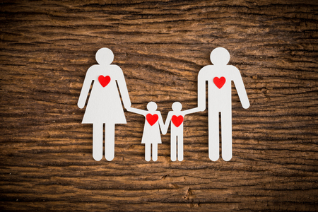 paper chain: paper chain family and red heart symbolizing on wooden background. love family concept
