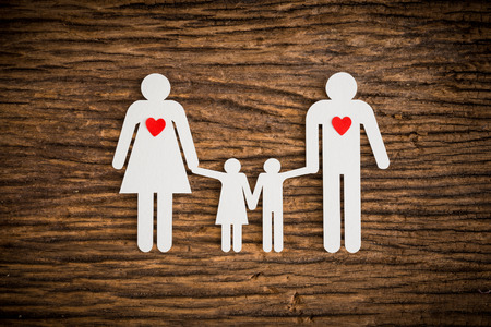 disorient: paper chain family and red heart symbolizing on wooden background. love family concept