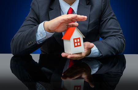 seguros: El hombre de negocios que sostiene una casa modelo. Concepto de seguro de hogar