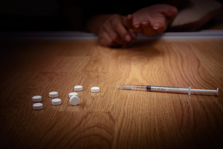 overdose male drug addict hand, drugs narcotic syringe on floor