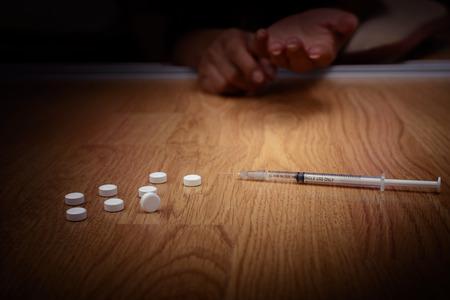 sobredosis: Sobredosis de la mano masculina adicto a las drogas, jeringuilla drogas estupefacientes en el piso Foto de archivo