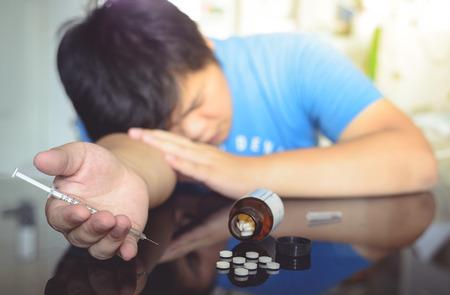 sobredosis: El hombre se derrumbó después de una sobredosis de fármacos, drogas Tablet. A mano con una jeringa Foto de archivo