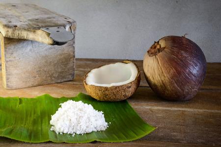 aceite de coco: cocos frescos y copos de coco en hoja de plátano y rallador de coco vieja Foto de archivo