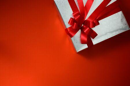 background red: Vista superior de la plata reluciente Embalado presente recipiente en el fondo rojo de la vendimia