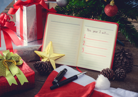 blank page: New Year Resolution, Empty list. on wooden table with colorful Christmas decorations